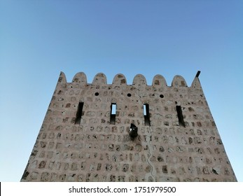 Traditional stone, coral and adobe watchtower and rampart of ancient Al Hisn fort in Sharjah emirate, United Arab Emirates. The watchtower has openings from which weapons could be fired at invaders.