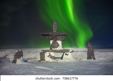 A traditional stone inukshuk, an Inuit cultural symbol used as a landmark to guide travelers in the far north, showing they are on the right path. Shimmering green aurora borealis in the background.