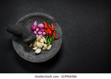 Traditional stone motar & pestle from Asia with spicy ingredients chilli, garlic & small purple onions.