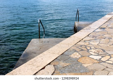 Traditional stone pier leading to two smaller concrete piers with inox handrails for easier entrance and clear blue sea in background on cold rainy day