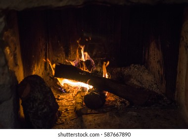 Traditional stone-made fireplace with burning wood  in mani province of peloponnesus peninsula of Greece