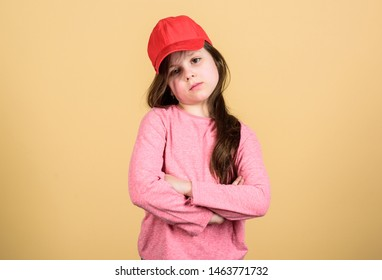 In traditional streetwear style. Adorable small child wearing baseball cap in casual style. Cute little girl with pretty face and long hair style. Kids street fashion and style.