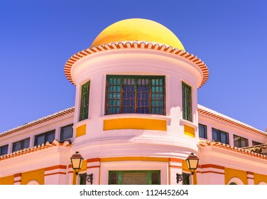 Traditional style white building with moorish influence. A yellow orange dome and green wood framed windows in Vila Real de Santo Antonio, Algarve, Portugal