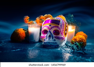 "Traditional sugar skull used at mexican offerings or ""ofrendas"" for Day of the Dead celebration with marigold or ""cempasuchil"" flowers. high contrast image"