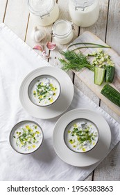 Traditional summer cold soup of homemade yogurt, cucumbers and fresh herbs on a wooden table