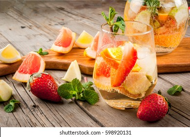 Traditional summer drink white sparkling sangria. With champagne, strawberries, oranges, lemon, green apple and grapefruit. On a wooden rustic table, with a jug and ingredients. Copy space.