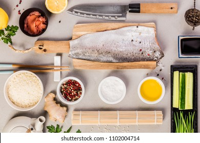 Traditional sushi ingredients: rice, salmon filet, ginger, cucumber, chives, soy sauce and bamboo mat on grey concrete background. Asian food background. Top view, flat lay.
