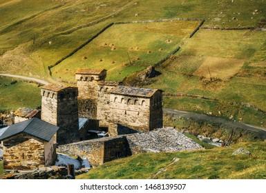 Traditional Svan Towers and machub houses with flagstone in Ushguli commune against big grass hills, Upper Svaneti, Georgia