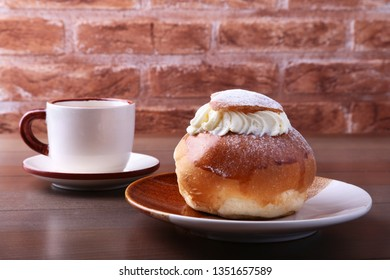 Traditional swedish dessert Semla, also called Shrove bun, with almond paste and whipped cream filling.