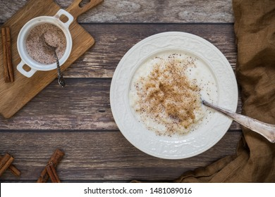 Traditional Swedish rice pudding with ground cinnamon flat lay from above perspective. There is a small bowl with cinnamon and sugar on a wooden chopping board next to the food.