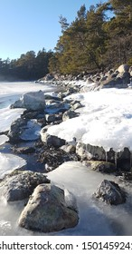 Traditional swedish sunny winter day along the seaside with snow, ice, forest and stones