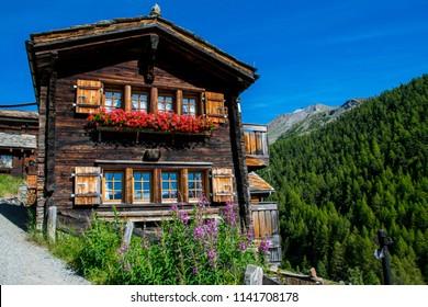 Traditional Swiss Chalet at Zermatt, Switzerland. The wooden warm house in green summer Pennine Alps. Best properties in Europe.