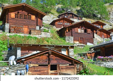 Traditional Swiss Mountain chalets in a mountain summer hamlet with small farm in the foreground