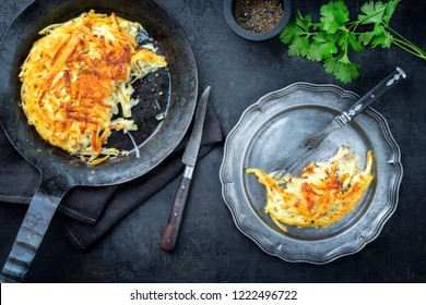 Traditional Swiss rosti as side dish with leek as top view in a frying pan and a pewter plate