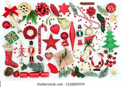 Traditional symbols of Christmas with retro and new bauble decorations, winter flora, food, gift boxes, food, ribbons and bows on rustic white wood background. Top view.