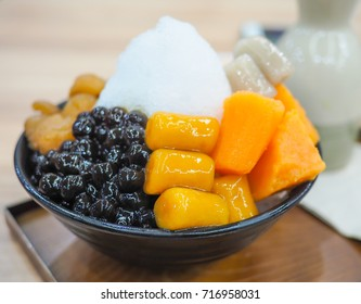 Traditional Taiwanese Dessert with brown sugar jelly, sweet potato and boba eating with snow ice