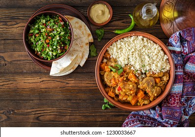 Traditional tajine dishes, couscous  and fresh salad  on rustic wooden table. Tagine lamb meat and pumpkin. Top view. Flat lay
