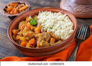 Traditional tajine dishes, couscous  and fresh salad  on rustic wooden table. Tagine lamb meat and pumpkin.