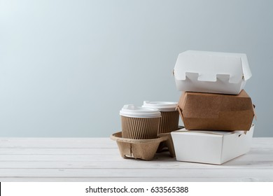 Traditional take-out coffee, two cups in holder, microwaveable take-out food paper boxes, close-up. Wooden background, place to insert your text. Food delivery.