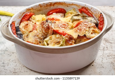 Traditional tasty rustic stew of chicken and vegetables, decorated with tomatoes, peppers and cheese