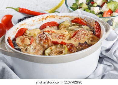 Traditional tasty rustic stew of chicken and vegetables, decorated with tomatoes, peppers and cheese.  With Greek salad and black olives