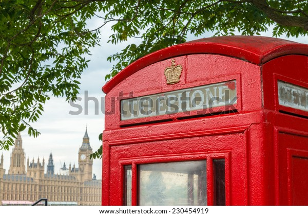 Traditional telephone booth along river Thames, Westminster Palace on background.