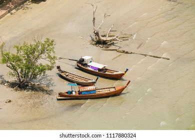 Traditional Thai boats are moored on the shoals of the beach