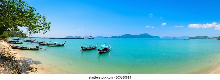 Traditional Thai boats for tourist near the beach Thailand. Panorama of Panwa Bay Phuket.