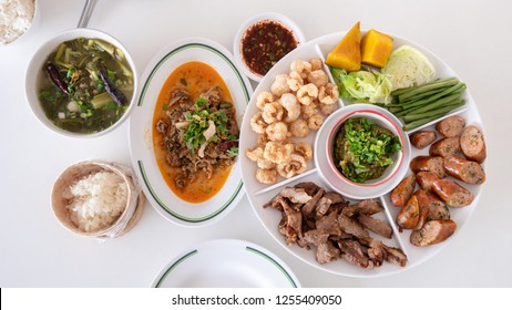 Traditional Thai food meal in Northern style combination with local chili paste appetizer (sour sausages, crispy skinned pork, grilled pork), spicy minced meat, vegetable sour soup and sticky rice