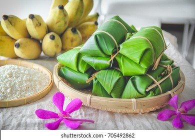 Traditional Thai food style, Glutinous rice steamed in banana leaf ( Khao Tom Mat or Khao Tom Pad ) bananas and sticky rice inside on wicker basket in culture market at Thailand