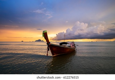 Traditional thai long tail boat on the sunset with colorful cloudy sky on background. Andaman Sea, Krabi Province of Thailand.