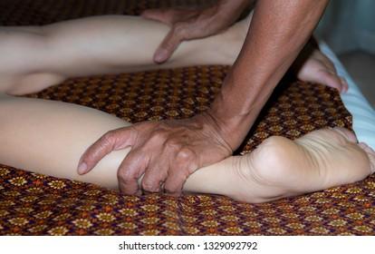 Traditional Thai massage,Young woman Breema bodywork while enjoying the acupressure techniques,Thai medicine,Thai tradition chiropractic therapy,Thai cosmetics,Thai reflexology spa benefits,
