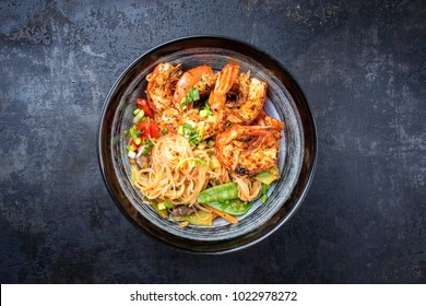 Traditional Thai Phak Kung curry with barbecue king prawns and noodles as top view in a bowl