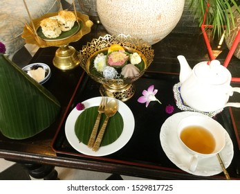 Traditional Thai sweets on leaf banana and gold plate. Tea pot and tea cup.