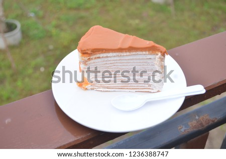 Traditional Thai Tea Flavored Crape Cake Served On A White Plain Dish Along With Pair