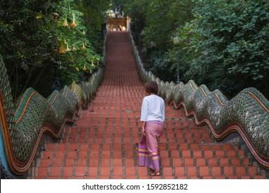 Traditional Thai Woman walking up the Naga Stairway, Doi Suthep Temple ,Chiangmai Thailand