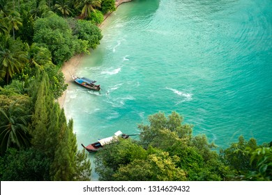 Traditional Thai wooden boat on a wild beach with lush jungle, blue water in the Bay