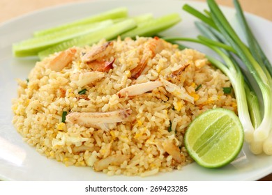 Traditional Thai-Style Fries Rice with Crab Meat on White Plate with a Piece of Lime, Cucumber Slices and Scallions