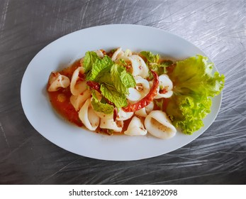 Traditional Thai-Style Spicy Squid Salad with Herbs on Steel Table