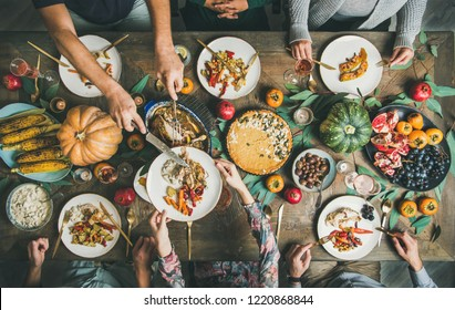 Traditional Thanksgiving day celebration party. Flat-lay of Friends or family eating different snacks and roast turkey or chicken at Festive Christmas table, top view