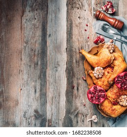 Traditional Thanksgiving day celebration party. Roasted chicken with pomegranate and garlic on wooden background. Friends or family dinner. Festive Christmas table. Top view