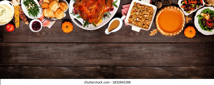 Traditional Thanksgiving turkey dinner. Above view top border on a dark wood banner background with copy space. Turkey, mashed potatoes, dressing, pumpkin pie and sides.