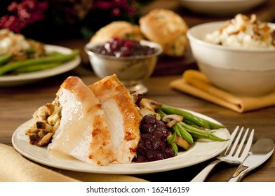 Traditional thanksgiving turkey dinner with cranberry sauce, stuffing, green beans, mushrooms and mashed potatoes.
