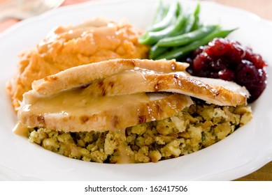 Traditional thanksgiving turkey dinner with cranberry sauce, stuffing, green beans and sweet potato casserole.