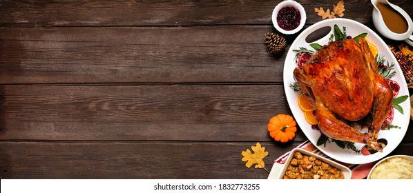 Traditional Thanksgiving turkey dinner. Overhead view side border on a dark wood banner background with copy space.