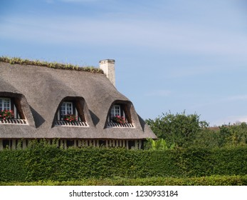 Traditional thatch in Normandy, France. | Traditional thatched house with garden in Normandy, France. |  Traditional thatched roof with windows and flowers in Normandy, France
