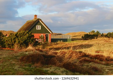 Traditional thatched house hidden in sand dunes on the North Sea Island Fanoe, Denmark
