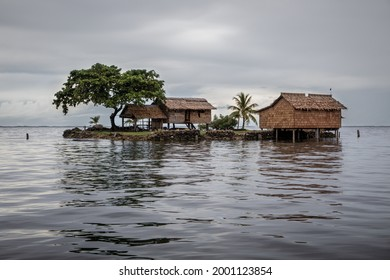 Traditional thatched houses on a small artificial island on a gloomy day in Lau Lagoon, off the island of Malaita in the Solomon Islands.