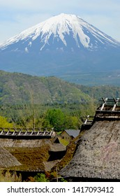 Traditional thatched roofs of a Japanese village and forest-covered hills stand at the base of Mt Fuji. The sky is blue with soft white clouds.