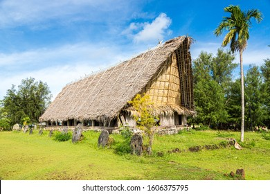 """Traditional thatched yapese men's meeting house called faluw (fale) and a """"bank"""" of historic megalithic stone money (rai) in front of it. A high coconut palm. Yap island, Micronesia, Oceania."""
